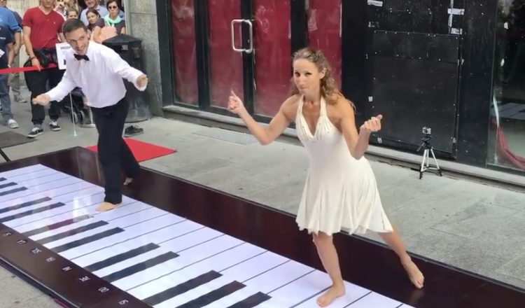 couple plays the pink panther theme on big piano